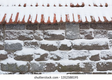 Stone wall and snow at winter day background