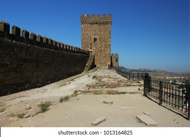 A stone wall and a tall tower of an ancient fortress.