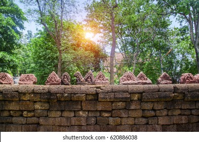 Stone wall and top of statue Buddha with sunlight at temple,Thailand