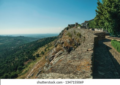 Stone wall and tower of Castle over rocky ridge, with hilly landscape covered by trees, in a sunny day at Marvao. An amazing medieval fortified village perched on a granite crag in eastern Portugal.