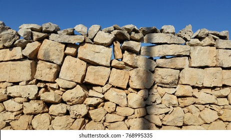 A stone wall under construction. No morter, as different size stones are fitted like a jigsaw puzzle to fill in all gaps.