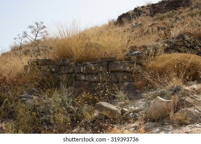Stone walls, about three thousand five hundred years old, forming part of a Minoan settlement at Myrtos, Crete, now overgrown with plants and grasses, parched in the summer heat.