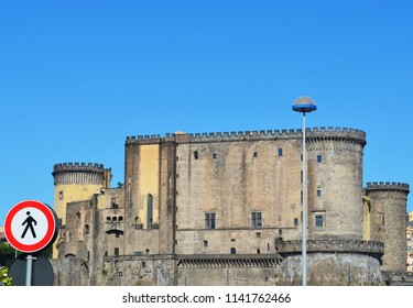The stone walls of the Castle Nuovo, Naples rise, against a clear blue sky. A red and black pedestrian sign is prominantly displayed, and a street lamp makes a contrasting modern feature.