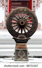 Stone wheel of Dharma near wall of buddhist temple in wat Tri Thotsathep, Bangkok, Thailand
