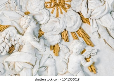 Stone white and gold bas-relief with angels in the clouds, Italy