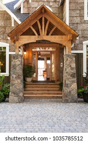Stone and wood front porch entryway to upscale country house with open front door and paving stone driveway. High quality residential home building materials.