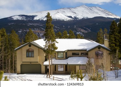 Stone and wood luxury home, with a beautiful Rocky Mountain backdrop, in the snowy winter.
