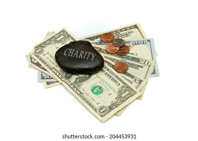 A stone with the word Charity engraved on it, rests on a fanned stack of dollar bills and change. Over white.