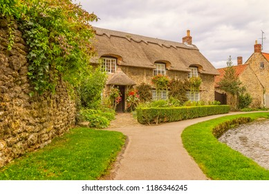 Stone-built picturesque thatched cottage in Thornton-le-Dale, North Yorkshire.  A path follows the curve of the river as it flows passed the house.