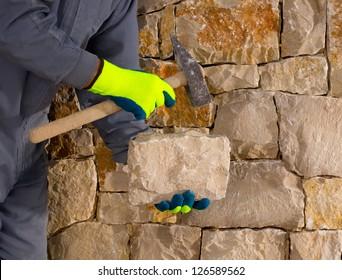 stonecutter mason with hammer and stone building a masonry stone wall
