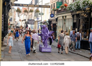 Stonegate, York, England, UK - August 05, 2011: The Stonegate in York City Centre packed with holiday makers and visitors looking in windows of shops and cafes. and in particular the 'Purple Man.