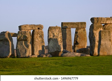 Stonehenge close up view with sun rays on stones, famous landmark in England. Sunset light. Summer evening. Salisbury UK.