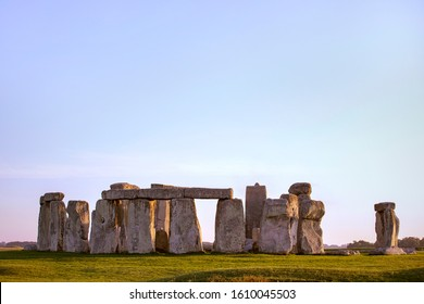Stonehenge general view with sun rays on stones, green grass, clear blue evening sky. Prehistoric monument in Salisbury, Wiltshire, England. Historic Neolithic Stones. No people.