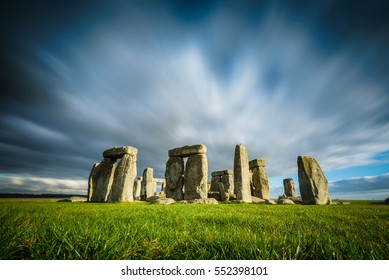 Stonehenge on a sunny and windy winter day. Ancient ruins in Wiltshire, England, with no people or tourists. Green grass in the foreground, moving clouds in the background.  High resolution wallpaper.