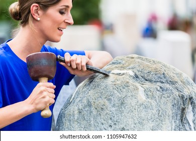 Stonemason working on boulder with sledgehammer and iron in workshop