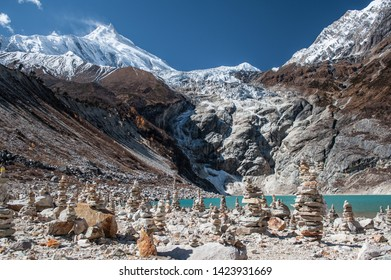 Stonemen and a  beautiful view of Manaslu mountain range, Birendra lake.  Lake and stone walls in front of snowy Mount Manaslu (8 156 meters) Birendra Lake, Himalayas, Nepal
