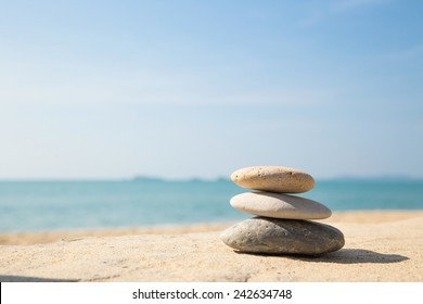 Stones balance, pebbles stack on the sand beach with shadow on right side , beautiful sea view during daytime on a sunny day with blue sky on background