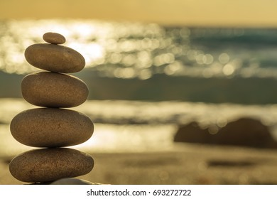 Stones balance, pebbles stack over blue sea and sunset