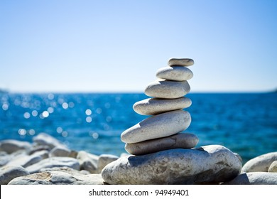 Stones balance, pebbles stack over blue sea in Croatia. Blue sky on sunny adriatic coast in summer.