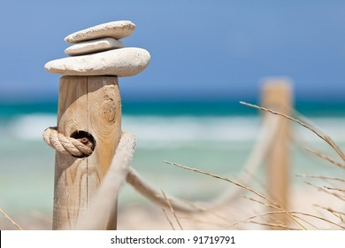 Stones balanced on wooden banister near the Trucadors beach.  Formentera island, Spain.