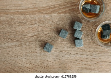 Stones for cooling whiskey and glases tulup on light wooden background