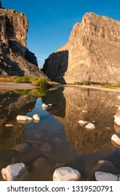 Stones covered with white salt in a shallow river, reflected in water. Santa Elena Canyon And Rio Grande. A view of Santa Elena Canyon in Big Bend National Park.