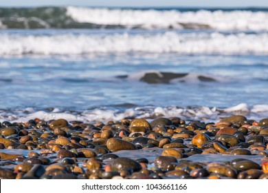 Stones covering South Carlsbad State Beach in San Diego, California with crashing waves in the background.