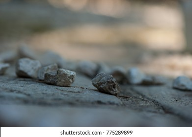 stones in the foreground and blur in the background, stones are light grey and the background grey and  orange colors, stones are in a group, the focus is on two stones and the others are blur