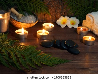 stones for hot massage are prepared on the table along with burning candles.