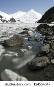 Stones, ice and snow capped mountains near alaskan Portage glacier