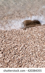 Stones on the beach with wave. Podgora, Croatia. Vertical photo