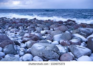 Stones on the coast of the Barents Sea in February twilight. Teriberka, Russia