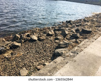 Stones on the embankment in the city. The embankment is made of stone - under the bright sunlight of the city. Embankment with a stone parapet by the river, in the rays of the setting sun.