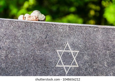 Stones on Jewish Memorial granite plate with Star of David. It is a Jewish tradition to take small stones and leave or put them on memorial plates of people you love, respect and never forget.