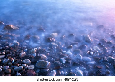 Stones on seashore at sunset on long exposure