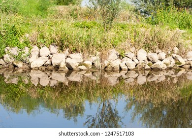 stones on the shore of the river that bounce off the water surface