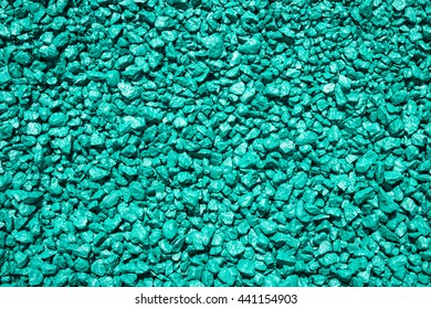 Stones painted in turquoise color. Decorative gravel. Turquoise pebble background texture