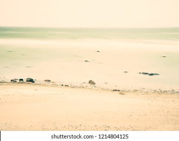 Stones and pebbles on sandy beach against foamy sea water.  Low angle view of beach sand with pebbles and mild waves.