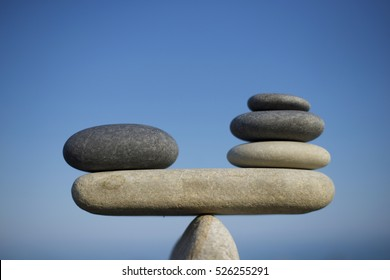 Stones pile background. Scales balance. Balanced stones on the top of boulder. To weight pros and cons. Close up. Balance of stones on a blue sky background with a copy space.