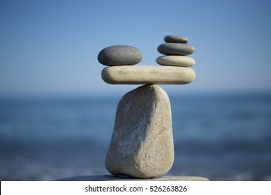 Stones pile background. Scales balance. Balanced stones on the top of boulder. Decide problem. To weight pros and cons. Balance of stones on a blue sky background with a copy space.