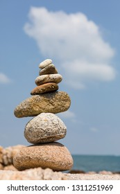 Stones pyramid with blue sky in background. Concept: symbolic, stability, zen, harmony, balance. Tropical sea beach.