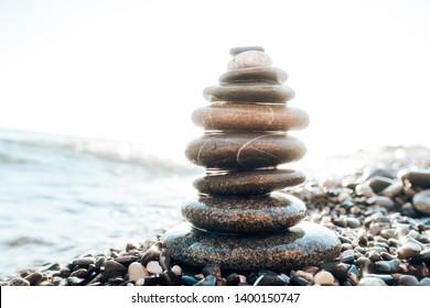 Stones pyramid on pebble beach, concept symbolizing stability, zen, harmony, balance and meditation, spa, massage, relax  Shallow depth of field.