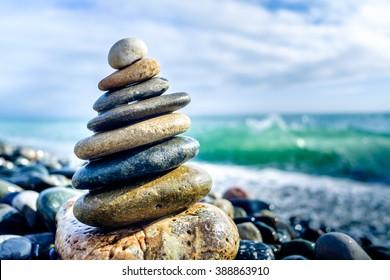 Stones pyramid on pebble beach symbolizing stability, zen, harmony, balance.