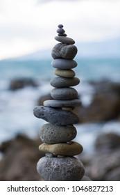 Stones pyramid on sand symbolizing zen, harmony, balance