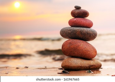 Stones pyramid on sand symbolizing zen, harmony, balance. Ocean at sunset in the background