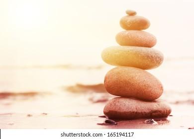 Stones pyramid on sand symbolizing zen, harmony, balance. Ocean at sunset in the background