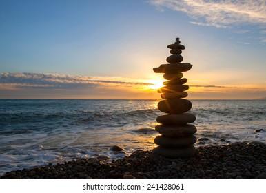Stones pyramid on sand symbolizing zen, harmony, balance. Ocean at sunset