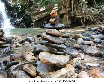 Stones pyramids balancing on the edge of a waterfall.