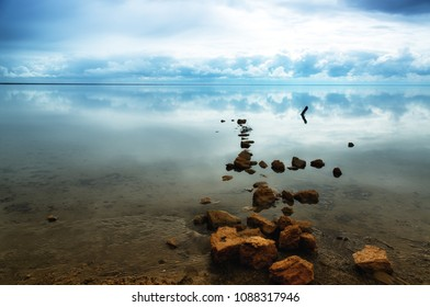 Stones and reflection of the sky in the salt lake of Elton, Russia
