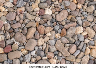 stones and river pebbles laid out evenly on the ground as the background